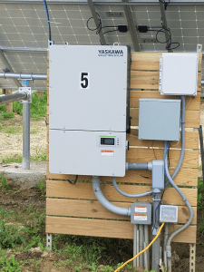 The PVI60TL inverter, mounted behind the array.