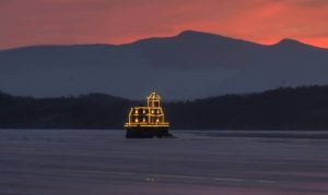 The winter sun sets behind the Hudson-Athens Lighthouse, bedecked in holiday lights. Used with permission from HALPS.