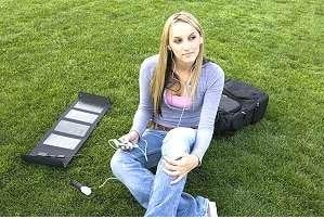 a young woman sits on grass listening to a music player powered by a portable solar panel