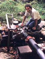 a man kneeling by a micro hydro power generator